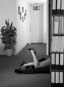 Woman lying atop man in office by shelves of files, low section